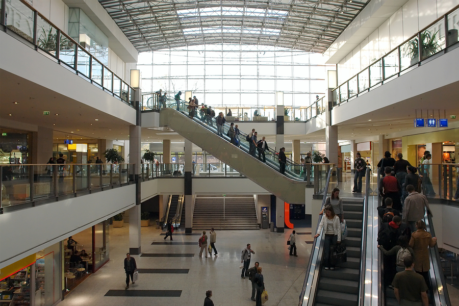 shoppers on elevators in multilevel shopping mall