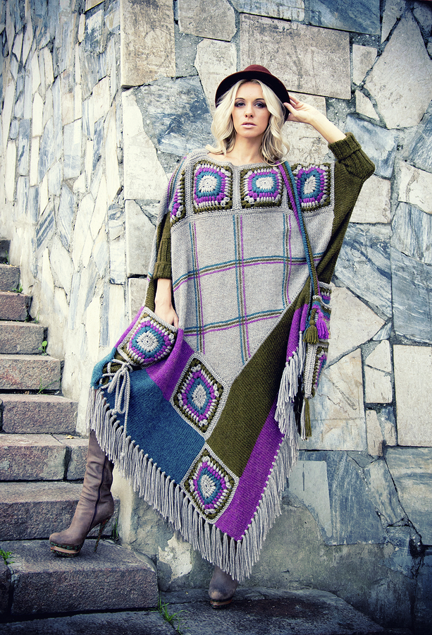 Beautiful blonde woman in designer clothes: warm poncho and hat