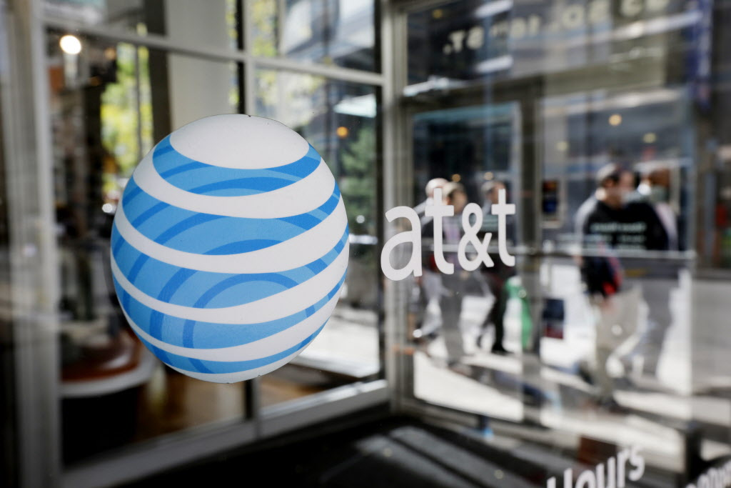 FILE - This Oct. 17, 2012, file photo, shows an AT&T logo on an AT&T Wireless retail store front, in Philadelphia. AT&T reports financial results on Tuesday, Jan. 26, 2016. (AP Photo/Matt Rourke, File)