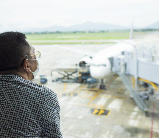 Persona con cubrebocas viendo por un cristal a una pista de aeropuerto